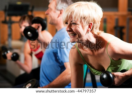 Three senior people - two women and one man - in the gym lifting dumbbells, exercising