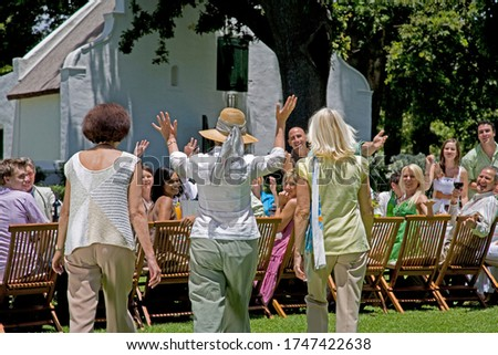 Three senior women arriving late to a summer garden party