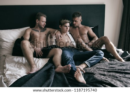 Three sexy guys on the bed.