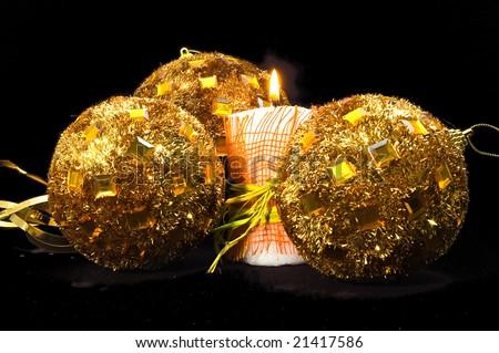Three shiny handmade christmas balls and candle on black bacground