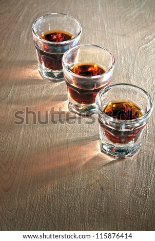 Three shot glasses full of dark colored alcohol on top of a bar table.