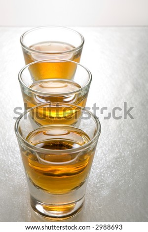 Three shots of scotch whiskey lined up in a row