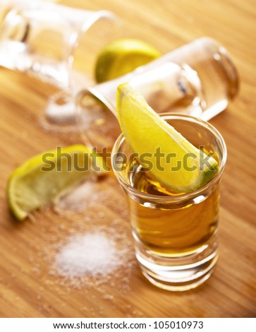 Three shots of tequila with lime and salt - stock photo