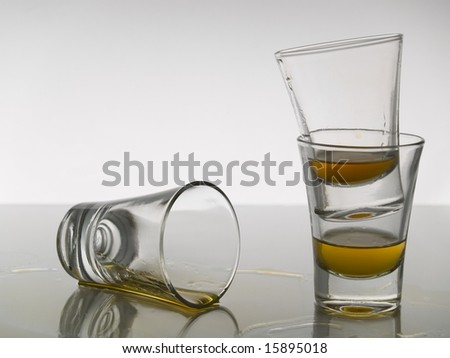 Three shots of whiskey on grey background over gray floor.