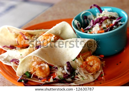 Three shrimp tacos and slaw on colorful plates