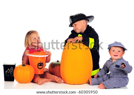 Three siblings dressed for Halloween as a cowgirl, fireman and train engineer with their pumpkins and trick-or-treat buckets.  Isolated on white.