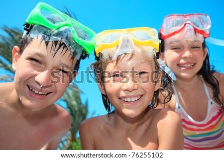 Three siblings in bathing suits, snorkels and diving masks.