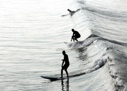 Three silhouettes of surfers in various stages of riding the same wave.