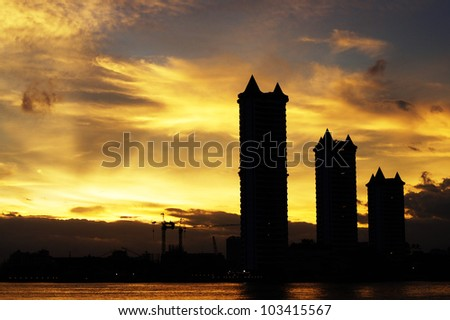 Three silluate buildings beside the river and the golden sky