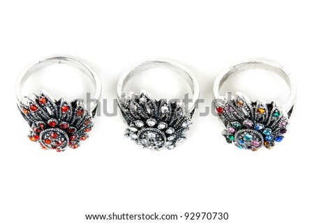 Three silver rings with precious stones on a white background