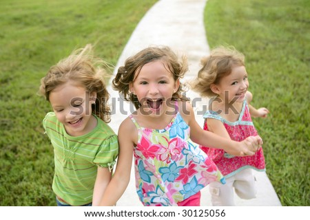 Three sister girls playing running on the green park outdoor