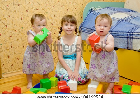 Three sisters - a  preschooler girl and two twins baby toy building of the blocks. Older sister teaching younger.