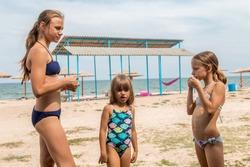 Three sisters on the beach in bathing bikinis