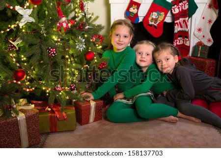 Three sisters posing in front of the christmas tree