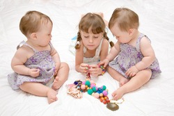 Three sisters - preschooler and baby twins playing with colorful  beads and ornaments. Education fashion and technology of manual work from infancy