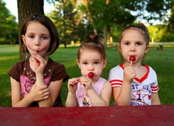 Three sisters sitting at a picnic table in a park eating lollipop suckers