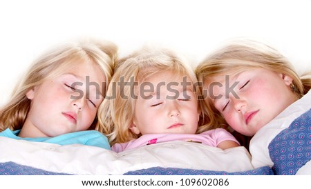 Three sisters sleeping or snuggling in bed