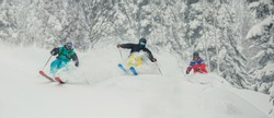 Three skiing friends moving downhill. Extreme downhill skier skiing in the snow in the pine and spruce forest. Descent in Sheregesh, Russia