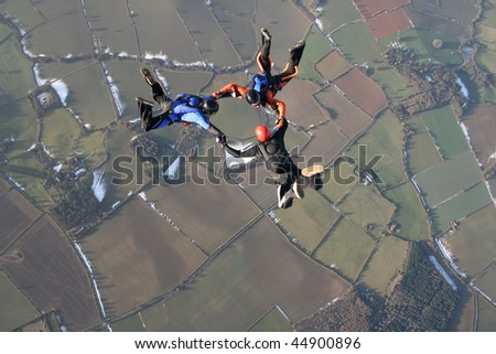 Three skydivers in free fall with snow in the background - stock photo