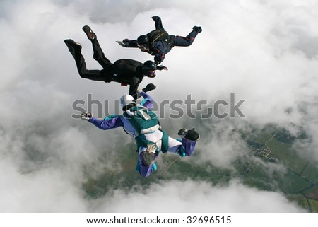 Three skydivers in freefall - stock photo
