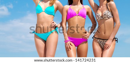 Three slim young girls in bikinis on the beach