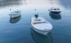 Three small blue and white fishing boat in calm water in the first blue morning light before sunrise
