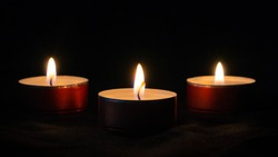 Three small candles in the dark