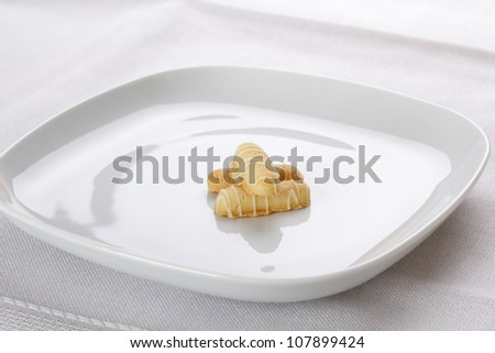 Three small cookies on the white plate.