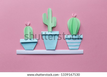 three small cute cactus of paper on a white shelf, pink background, free space #1339167530