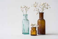 Three small glass handmade vases with white dried wild flowers. Brown and blue glass vintage bottles. Antique interior decoration objects.