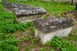 Three small old limestone gravestones in the Orthodox cemetery.