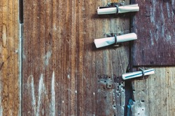 Three small rolls of white papers notification inserted into old rusty padlock hasp on the old wooden door. Bulletin sticking out at the gate of the abandoned house. Selective focus.