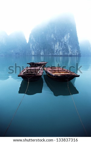 Three small row boats tendered behind a passenger Junk in a misty Halong Bay, Vietnam.