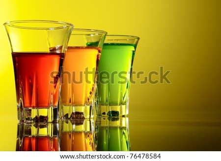Three small shot glasses of alcoholic beverages