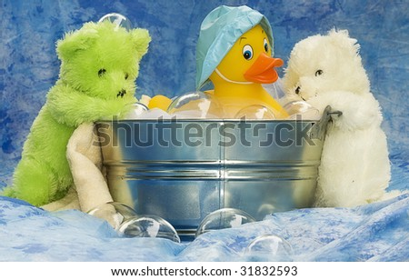 Three small toy animals, two teddy bears and rubber ducky playing in tub with the bubbles