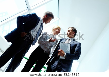 Three smart employees discussing new strategy at meeting