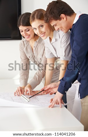 Three smiling architects working with a blueprint in their office