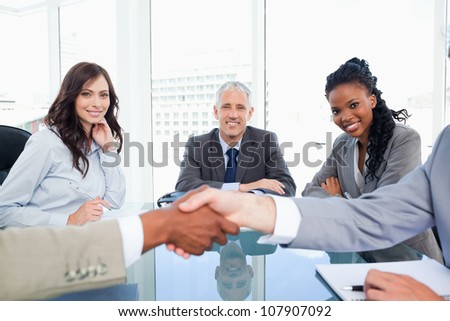 Three smiling colleagues looking at two executives shaking hands