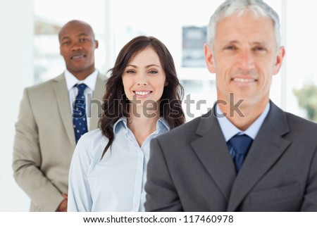 Three smiling executives standing upright and looking ahead