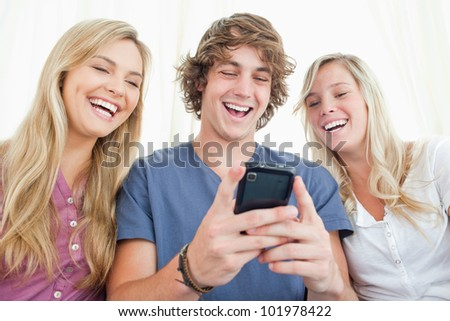 Three smiling friends sit together and look at the message on the man\'s mobile phone