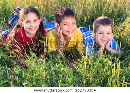 Three smiling kids lying on the green grass meadow