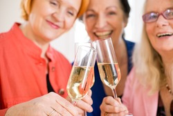 Three Smiling Mom Friends Tossing Glasses of Champagne  Celebrating their Friendship. Captured in Macro.