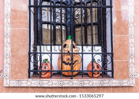 Three smiling pumpkins in a colonial window with traditional tiles, Merida, Mexico #1533065297