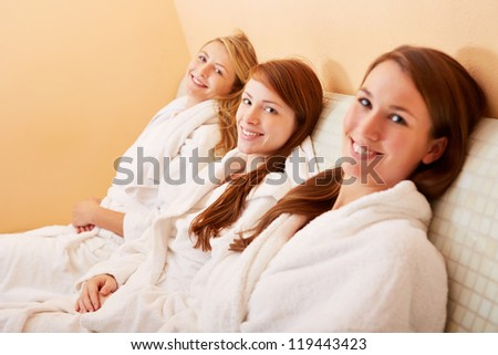 Three smiling relaxed women sitting on a heated bench after the sauna