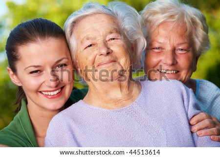 Three smiling women: mother, her daughter and granddaughter