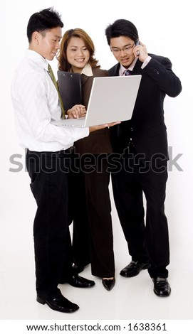 Three smiling young business people looking at a laptop computer