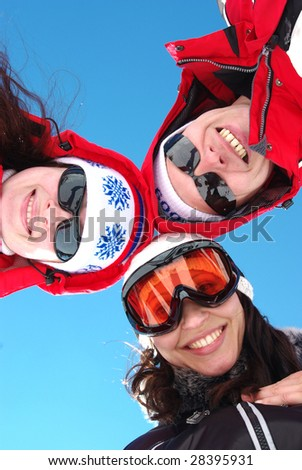 Three snowboarders standing in huddle, smiling, low ange view.