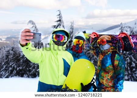 Three snowboarders taking selfie with smartphone camera at ski resort. Friends photographing for social network sharing with snowboards near forest wearing reflective goggles, colorful fashion clothes #1240718221