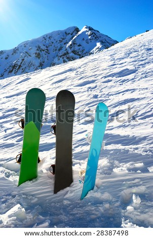 Three snowboards under sun with mountains behind