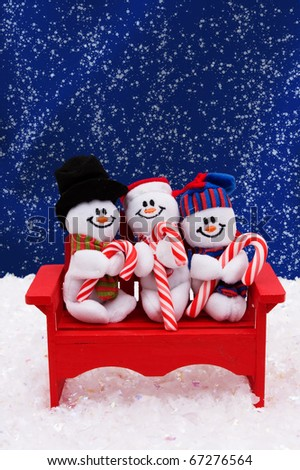 Three snowmen sitting on a bench with a night sky background, snowman having fun